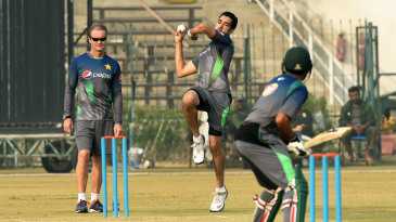 Grant Flower watches Umar Gul bowl during a practice session in Lahore