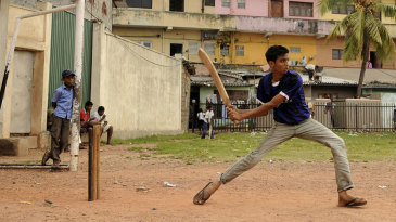 Boys play street cricket near the Premadasa Stadium