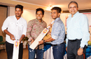 Mushfiqur Rahim hands over a bat to Under-19 cricketers Zakir Hasan (second from right) and Pinak Ghosh (left) at a promotional event, Dhaka, May 13, 2016