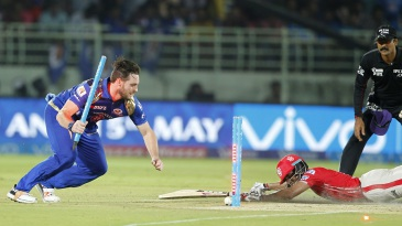 Mitchell McClenaghan uproots the stumps as he tries to run Wriddhiman Saha out