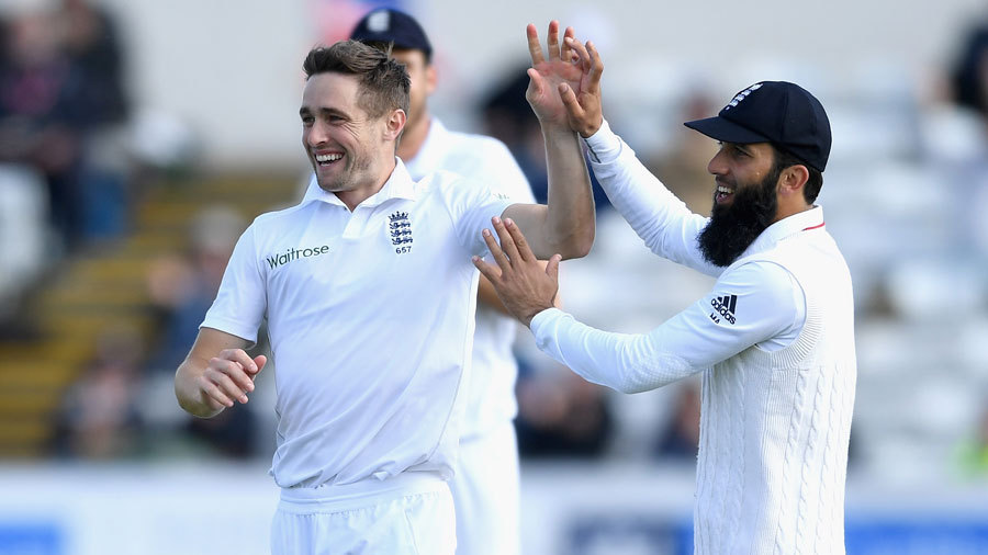 Chris Woakes gets a high five from Moeen Ali