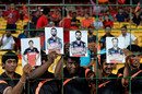 Fans hold up the photos of Royal Challengers Bangalore players: Shane Watson, KL Rahul, Virat Kohli and AB de Villiers, IPL 2016, Qualifier 1, Bangalore, May 24, 2016