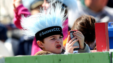 A young fan looks at his phone