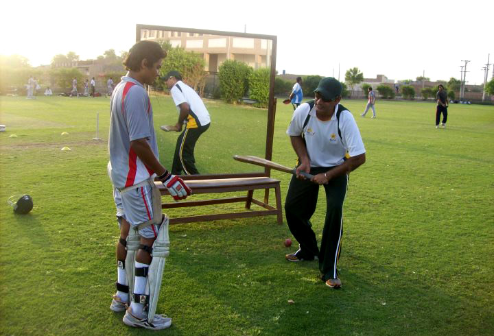 Moddershall A's Ijaz Ahmed Jr (right) gives some tips to a youngster