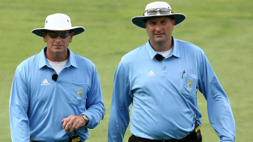 The umpires Paul Reiffel and Paul Wilson leave the field