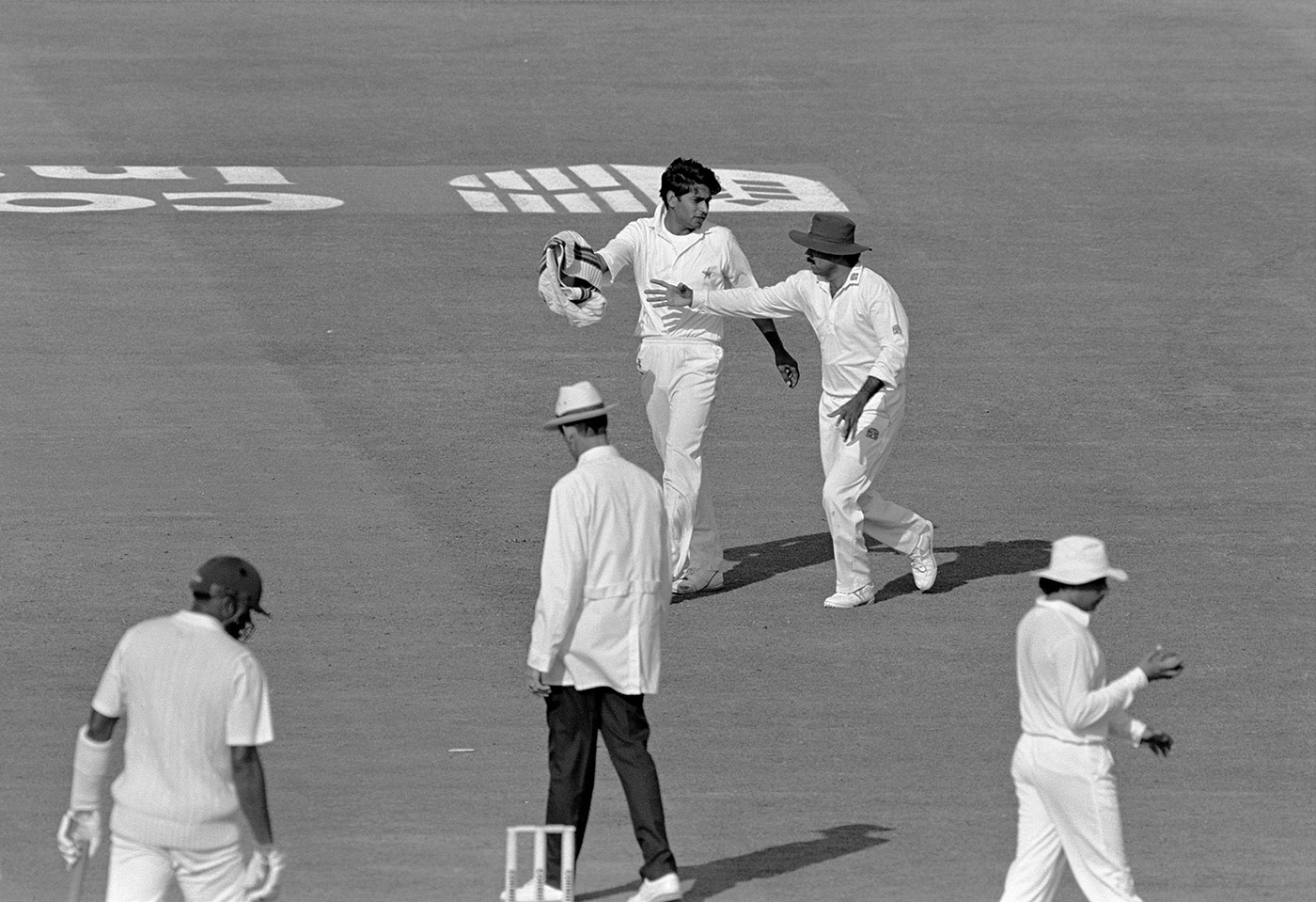 Sweatergate: Aaqib Javed and Javed Miandad after Aaqib's tugging match with umpire Roy Palmer (second from left) during a changeover at the Old Trafford Test