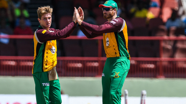 Adam Zampa and Martin Guptill celebrate the wicket of JJ Smuts