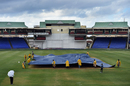 Groundsmen cover the pitch at Warner Park, WICB President's XI v Indians, Basseterre, 1st day, July 14, 2016