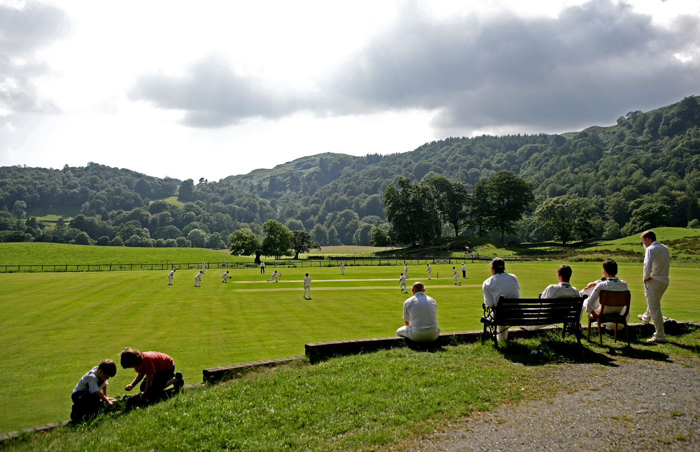 Players watch a game of village cricket from the boundary at Ambleside Cricket Club