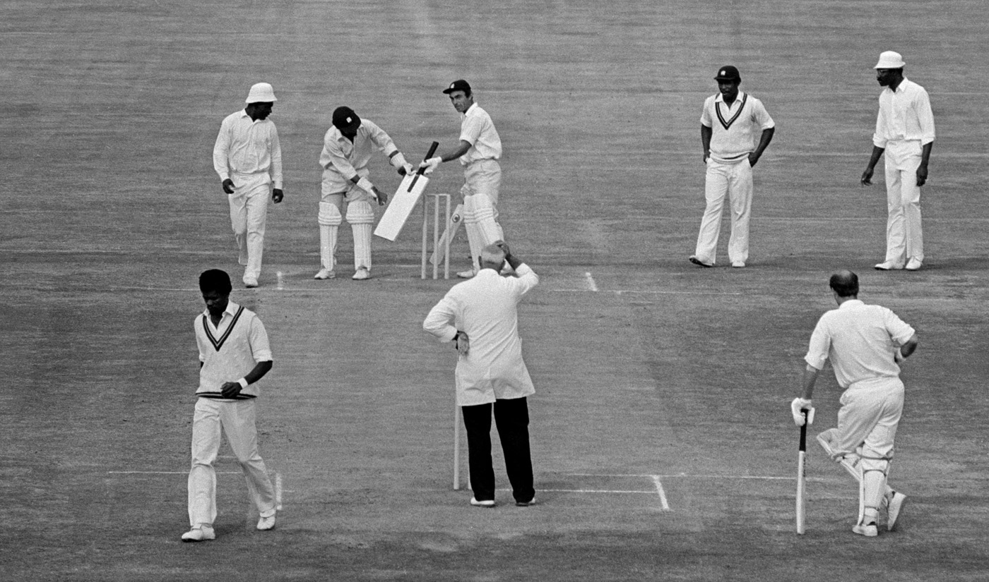 Need a battalion, not a bat: England batsman John Edrich hands over an extra-large bat brought to the field by a spectator to West Indies keeper Deryck Murray, Old Trafford, 1976