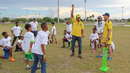 Kumar Sangakkara teaches local Florida kids how to bowl during a clinic put on by Jamaica Tallawahs, Florida, July 22, 2016