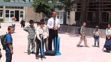 Khushal Khan High School children receiving tips from Taj Malik using Kwik cricket set donated by ECB