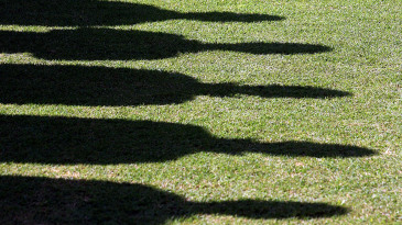 The shadows of players are seen as they stand in silence in memory of Bob Woolmer