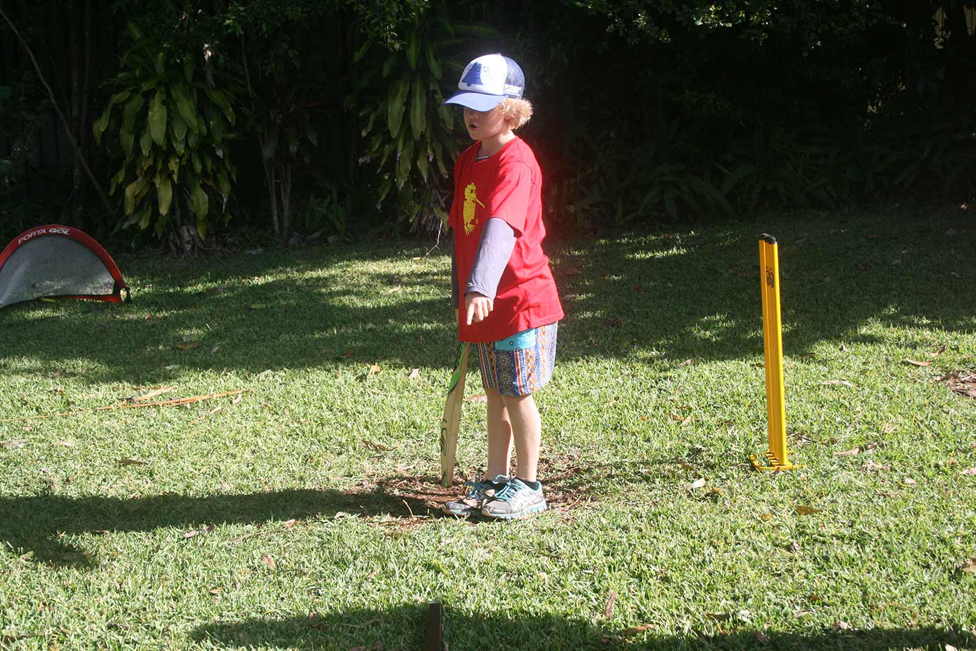 A boy stands at a backyard wicket