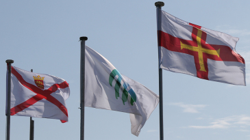 Jersey (left) and Guernsey (right) flags fly high at the start of play