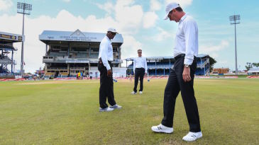 The umpires inspect the outfield at Queen's Park Oval