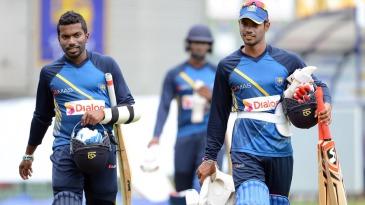 Amila Aponso and Dhananjaya de Silva walk with their batting equipment