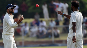 Suresh Raina tosses the pink ball to bowler Ashok Dinda