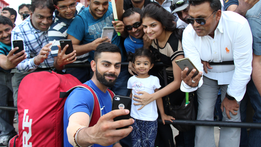 Virat Kohli takes a selfie with a young family after India's training session