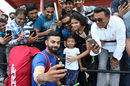 Virat Kohli takes a selfie with a young family after India's training session, Lauderhill, August 26, 2016