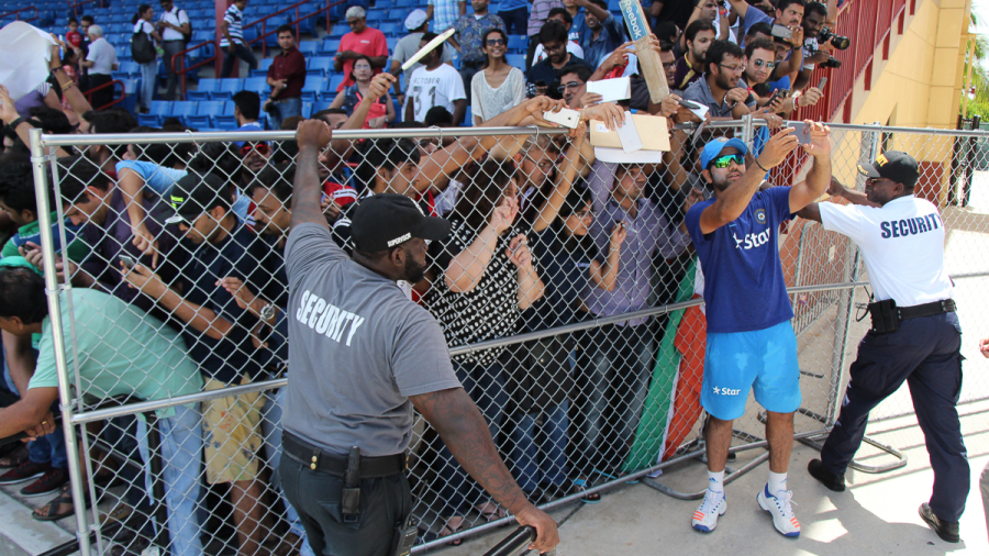 Security guards hold up a fence from collapsing under the weight of fans desperate for a selfie with Rohit Sharma