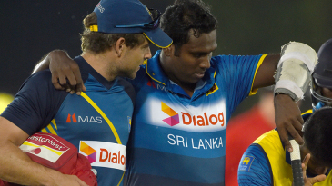 An injured Angelo Mathews is helped off the field