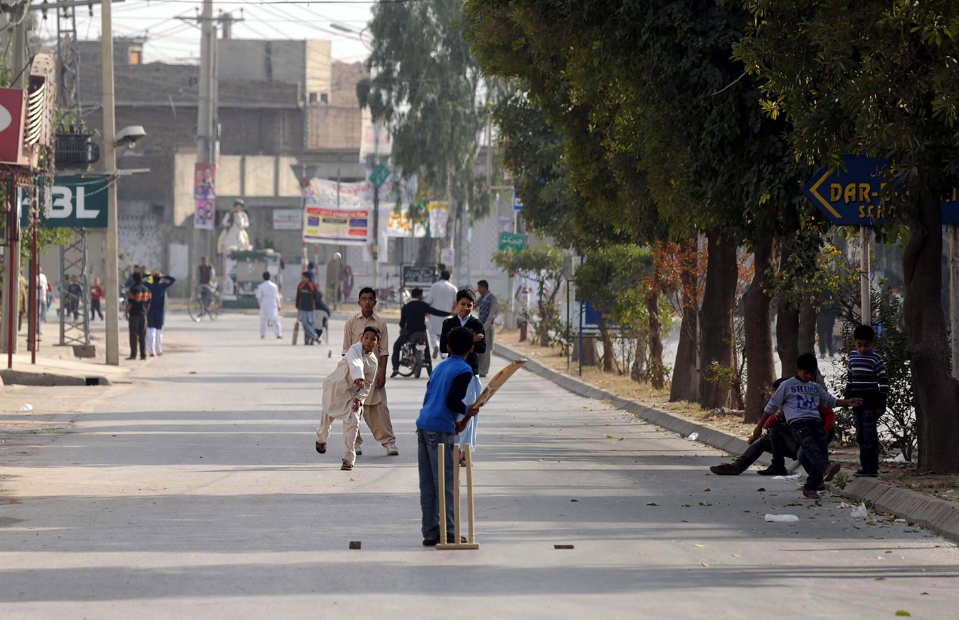 Kids play cricket in a street