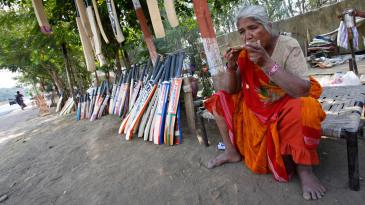A vendor sells cricket bats on the corner of a road in Nagpur