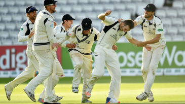 Middlesex's players mob Toby Roland-Jones after sealing victory in the County Championship