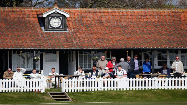 Players and spectators watch from the pavilion at Frinton on Sea
