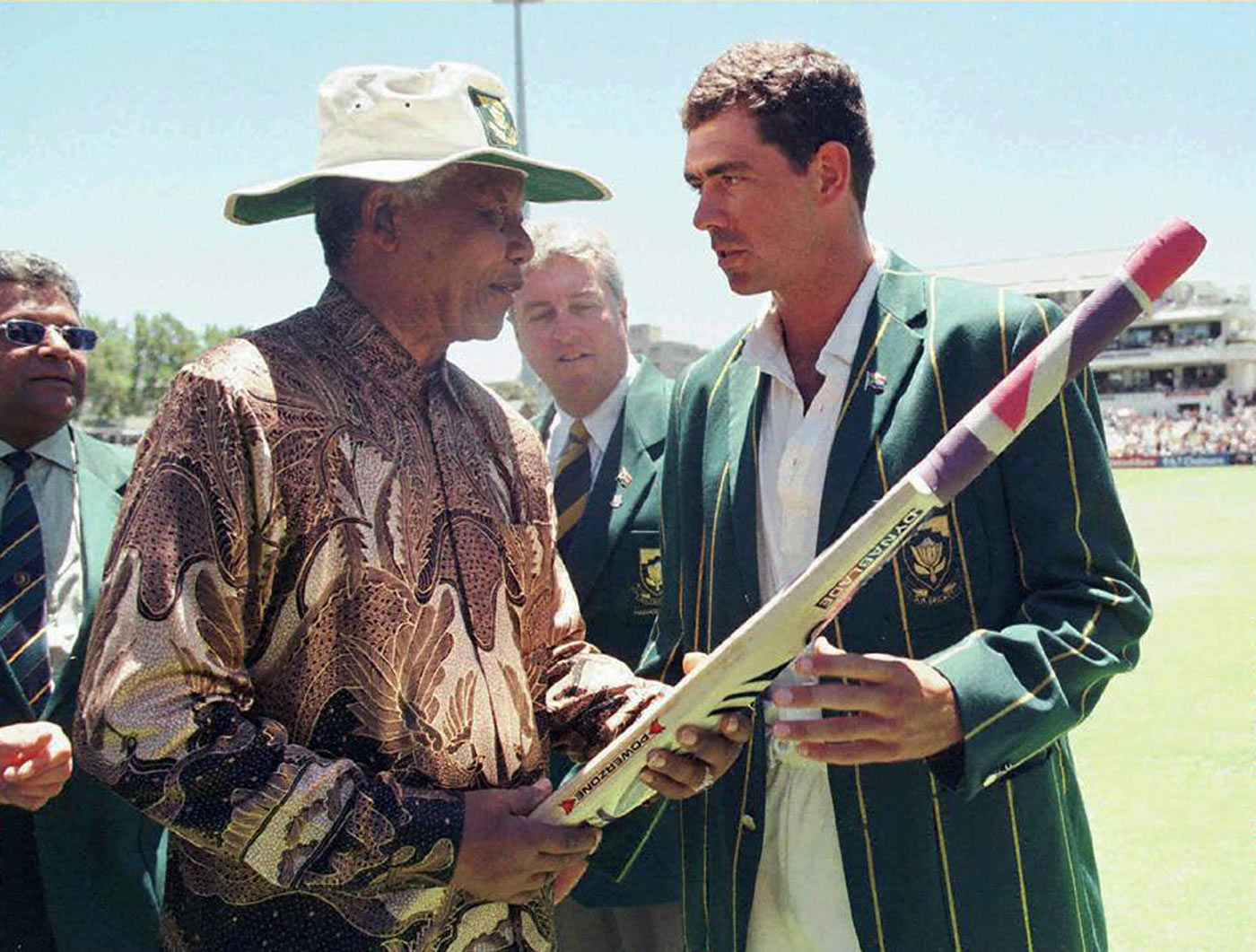 Nelson Mandela receives a cricket bat from Hansie Cronje