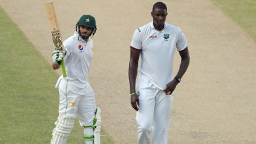 Azhar Ali celebrates his 150 as West Indies skipper Jason Holder walks by
