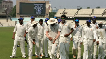 K Gowtham leads Karnataka off the field after their innings and 160-run win over Delhi in Kolkata