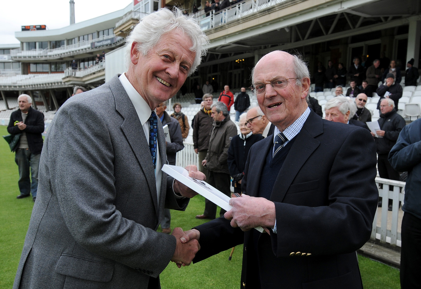 Pat Pocock (left), as Surrey's deputy president in 2014, presents certificates to members who had been with the club for 60 or more years