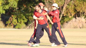 Charles Perchard celebrates after taking the wicket of Prashanth Nair