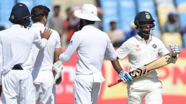 England's fielders watch as Cheteshwar Pujara successfully reviews his lbw dismissal
