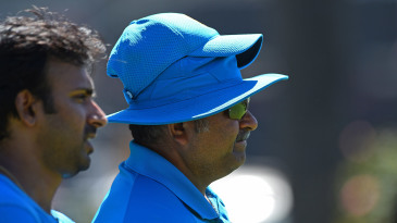 Bowling coach Bharat Arun (right) looks on
