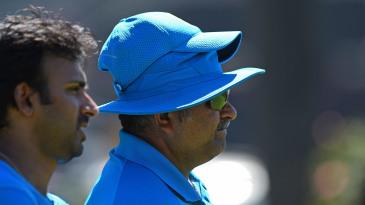 Bowling coach Bharat Arun (right) looks on