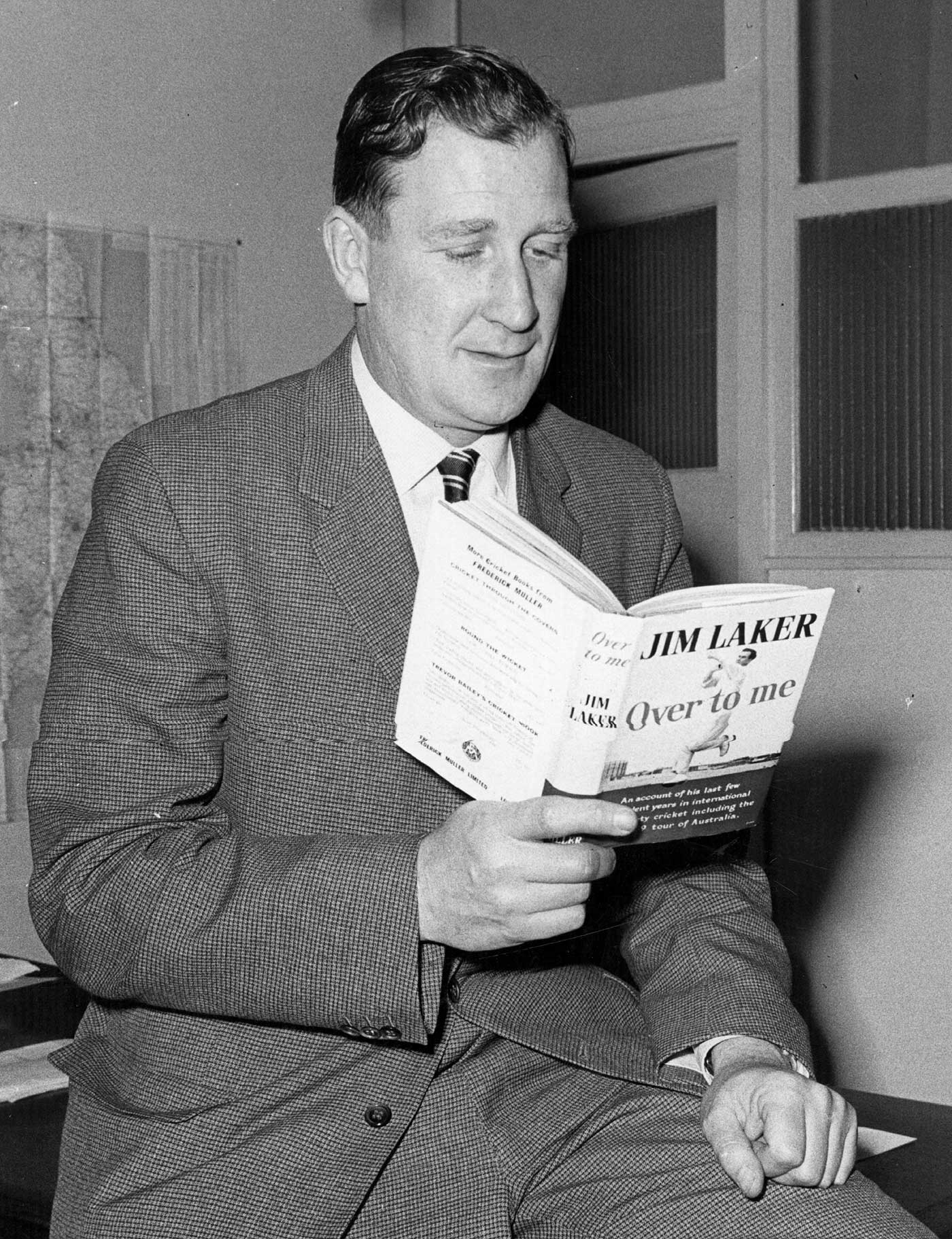 A ripping good yarn: Jim Laker reads his book <i>Over to Me</i>, in 1960