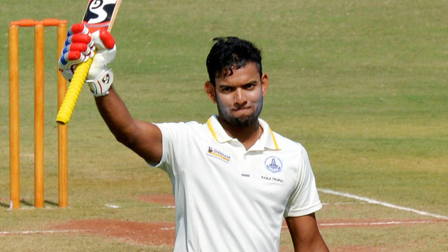 Kaushik Gandhi raises his bat after reaching his 150