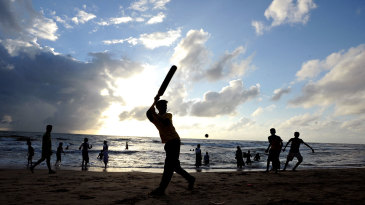 People play cricket on the beach in Colombo