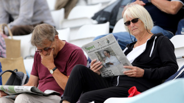 Spectators read the morning papers
