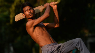 A youngster plays cricket in a park in Dhaka