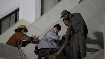 A guest at Regent Plaza Hotel in Karachi is helped to safety after a fire broke out at the hotel