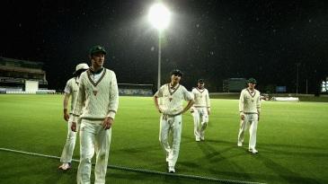 The Tasmania side walks off as the rain falls