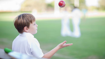A kid tosses a cricket ball in his hand