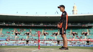 Scorchers coach Justin Langer inspects the pitch before the start of the game