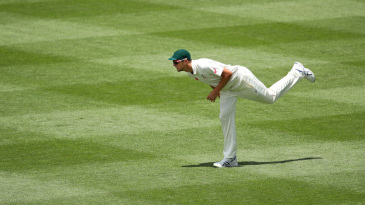 Josh Hazlewood stretches while fielding