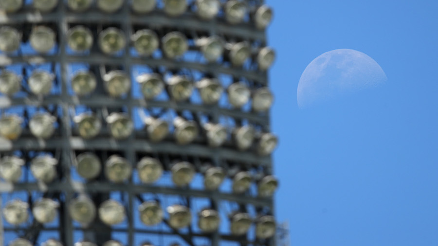 The moon was visible behind one of the light towers