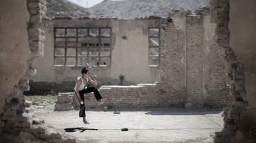 An Afghan boy runs up to bowl